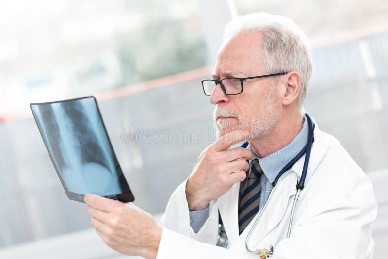 看X-射线的资深医生 免版税库存图片