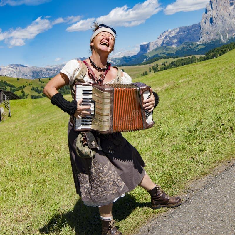 真假嗓音陡然互换唱在阿尔卑斯-唱和演奏手风琴的音乐家 免版税库存图片