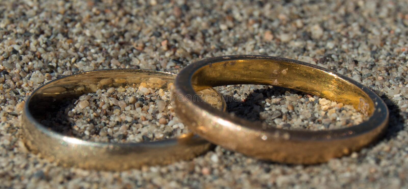 真实的恋人金黄对圆环在沙漠 库存图片