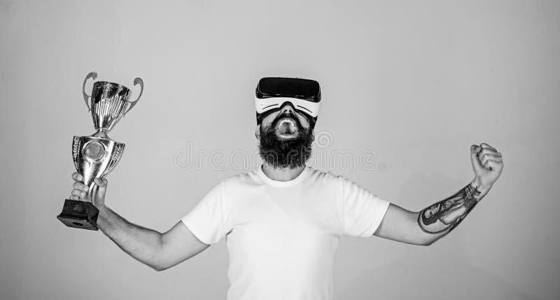 真正成就概念 戴VR眼镜的人获得了冠军,举行手中金黄觚 有胡子的人在VR 免版税库存照片