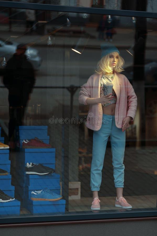 真正的女孩看起来一个玩偶在商店在销售中 女孩站立在淡色蓝色和桃红色颜色穿戴的陈列室 免版税库存照片