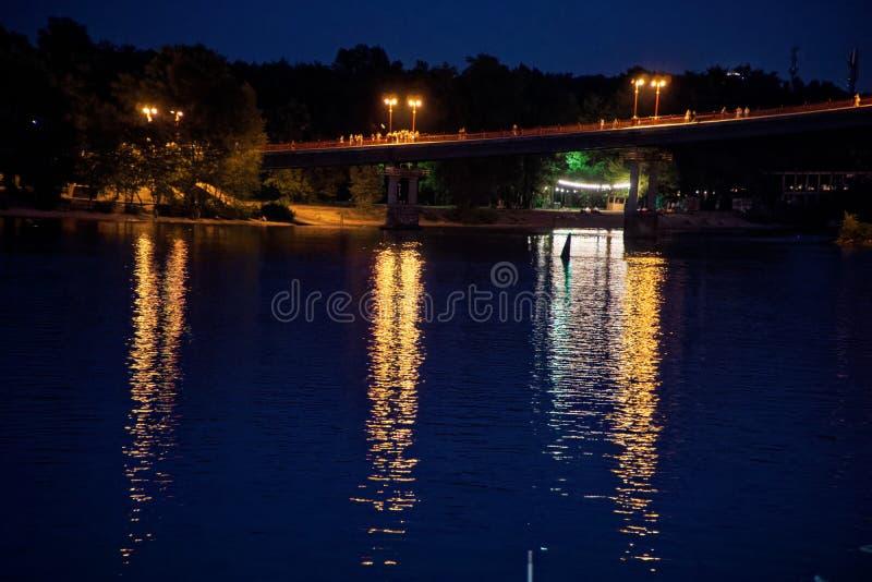眨眼睛在夜桥梁在水反射点燃,闪耀 库存图片