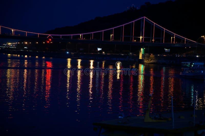 眨眼睛在夜桥梁在水反射点燃,闪耀 免版税库存照片