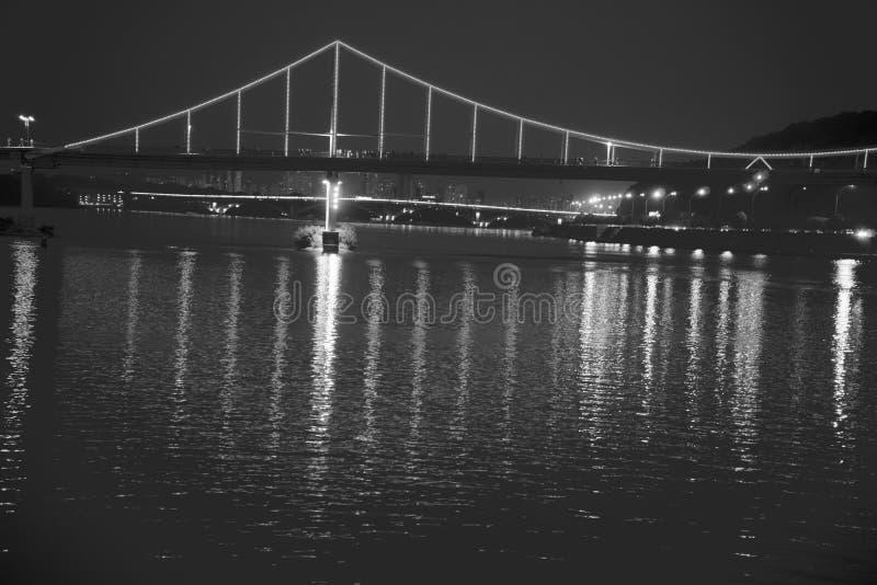 眨眼睛在夜桥梁,在水反射,单色图片的闪闪发光点燃 免版税库存图片