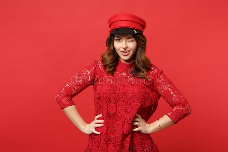 眨眼睛鞋带礼服的,与胳膊两手插腰的盖帽身分俏丽的年轻女人画象隔绝在明亮的红色墙壁上 免版税图库摄影