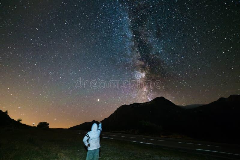 眺望看满天星斗的天空和银河的一个人在阿尔卑斯的高处 在左边的火星行星 冒险和exp 免版税库存照片