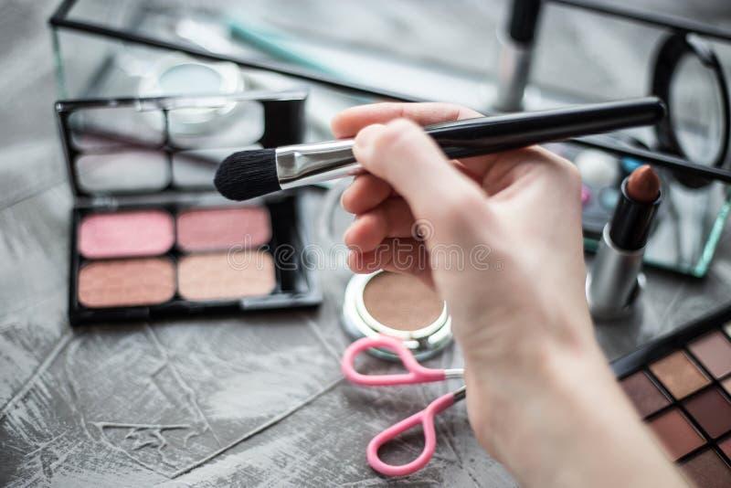 眼影膏刷子在女性手上 免版税库存照片