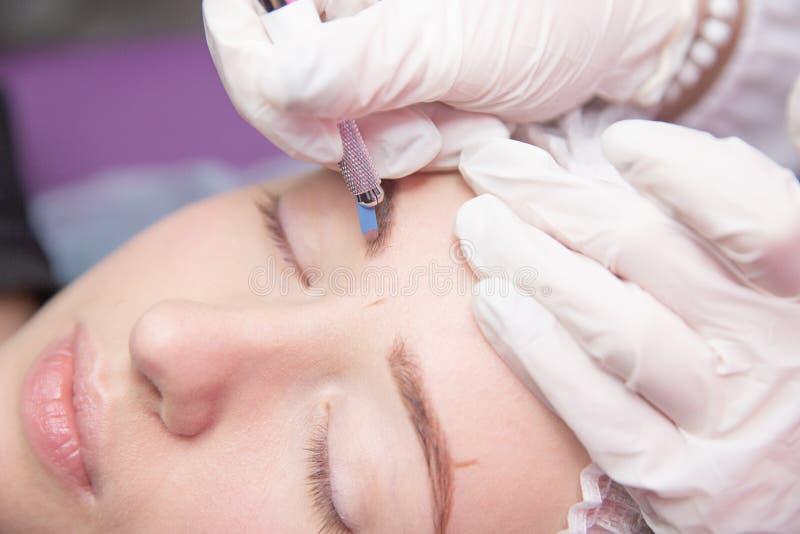 眼眉的永久构成 Microblading眉头 做眼眉的美容师刺字为女性面孔 美丽的年轻人 图库摄影