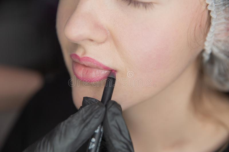 眼眉的永久构成 Microblading眉头 做眼眉的美容师刺字为女性面孔 美丽的年轻人 免版税图库摄影