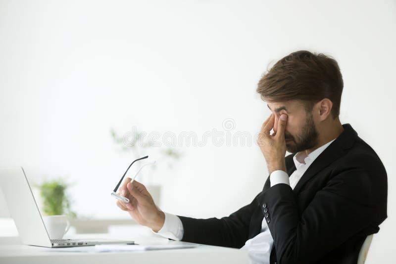 眼睛疲劳在工作,疲乏的被用尽的商人离开gla 免版税库存图片