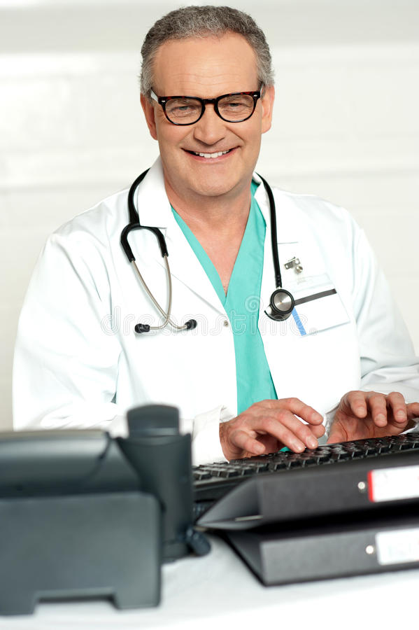 眼睛的微笑的医师佩带键入在关键董事会 免版税库存照片
