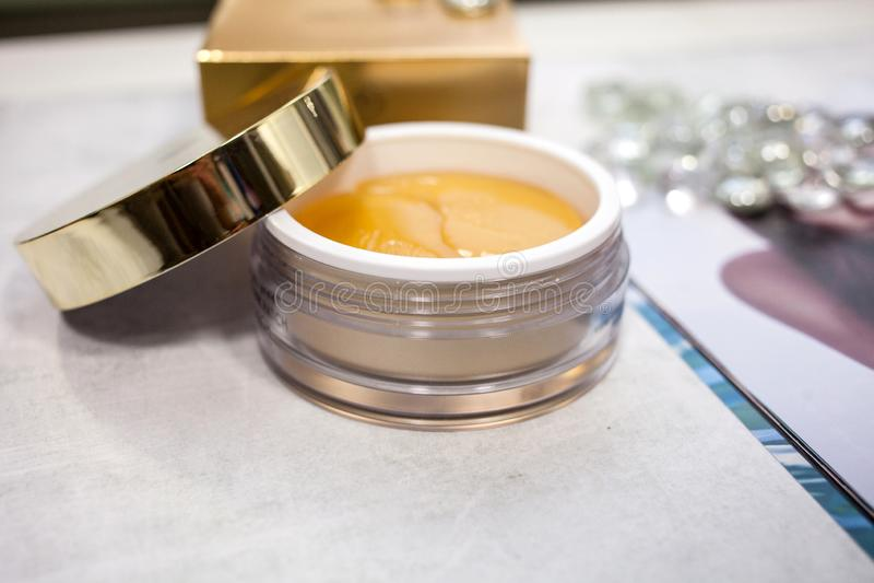 眼睛的金补丁在有一个开放盒盖和一个金黄箱子的一个瓶子在背景 秀丽和个人照料概念 图库摄影