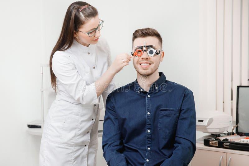 眼科医生妇女医生检查诊断眼力近视,远视年轻人 库存图片