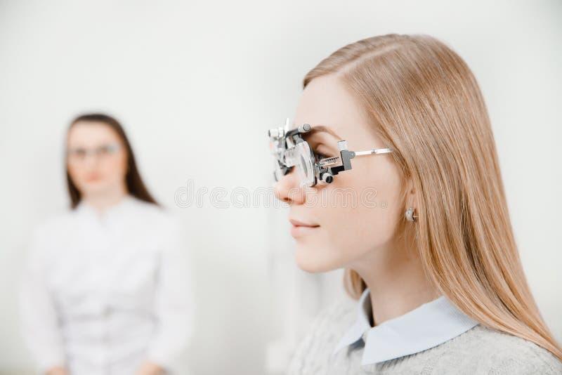 眼科医生妇女医生检查诊断眼力近视,远视年轻女人 免版税库存照片