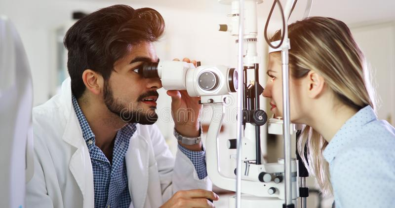 眼科学诊所的女孩妇女屈光率侦查的 库存图片