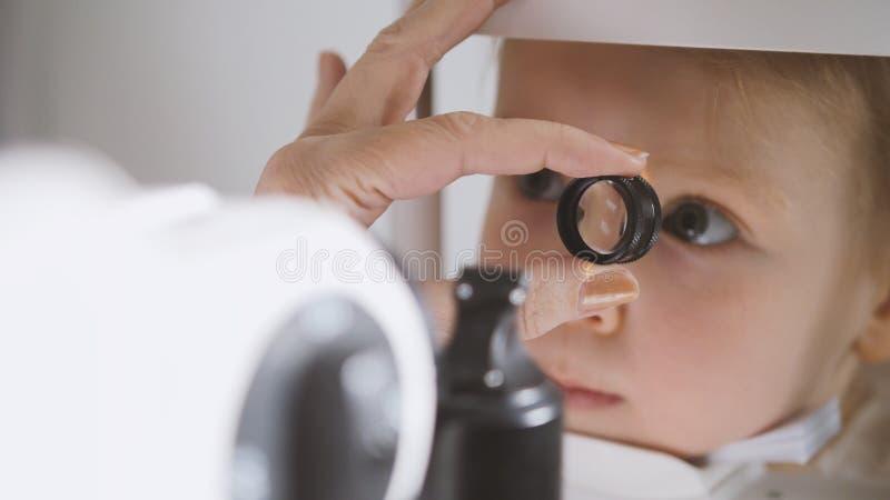 眼科学诊所的逗人喜爱的孩子-验光师诊断小白肤金发的女孩 免版税图库摄影