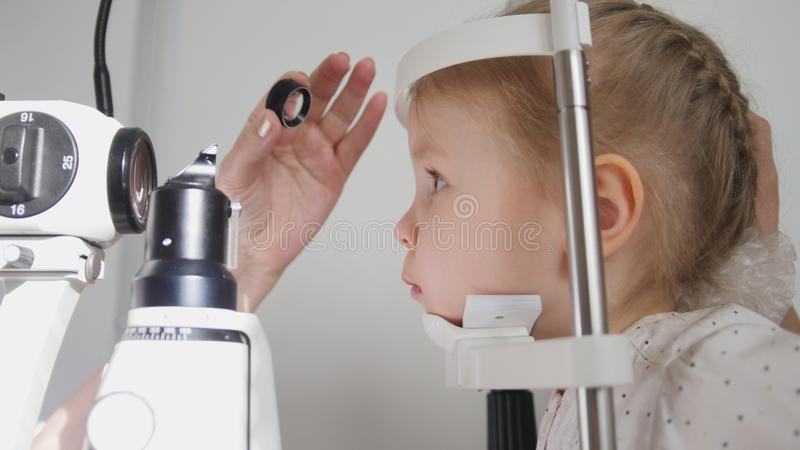 眼科学诊所的逗人喜爱的孩子-验光师诊断小白肤金发的女孩 免版税库存图片