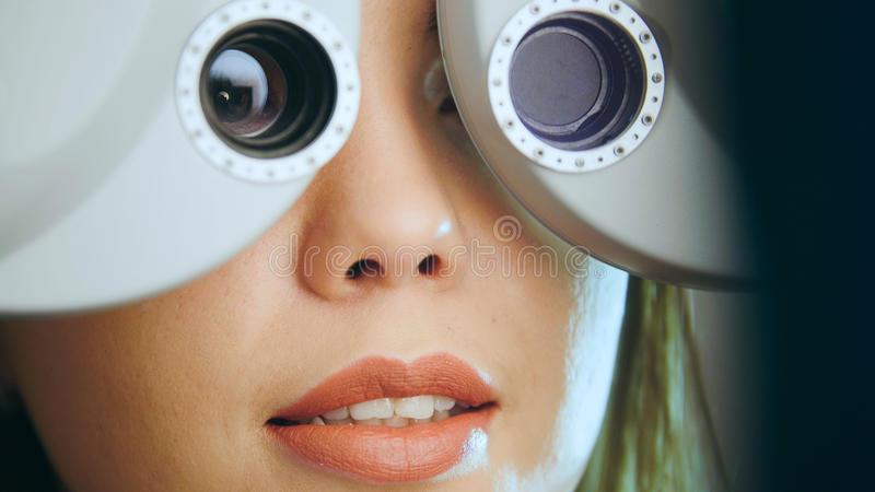 眼科学-少妇检查在现代设备的眼睛在医疗中心 图库摄影