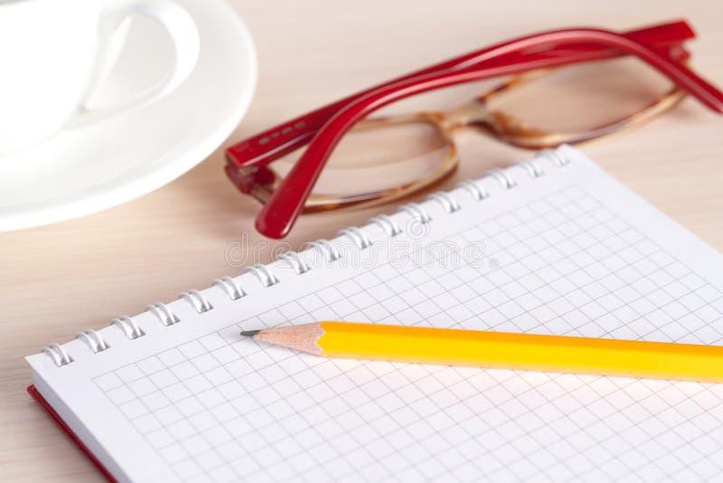眼镜、备忘录和茶杯 库存图片