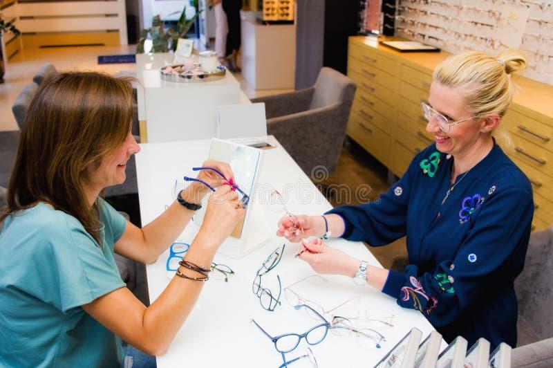 眼镜师有她的选择镜片的客户的沙龙女推销员 免版税库存图片