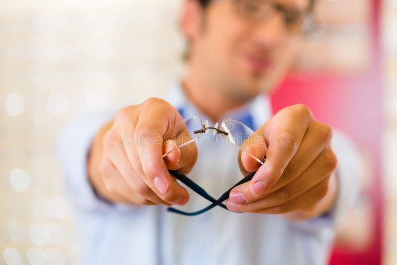 眼镜师的年轻人戴眼镜 免版税库存照片