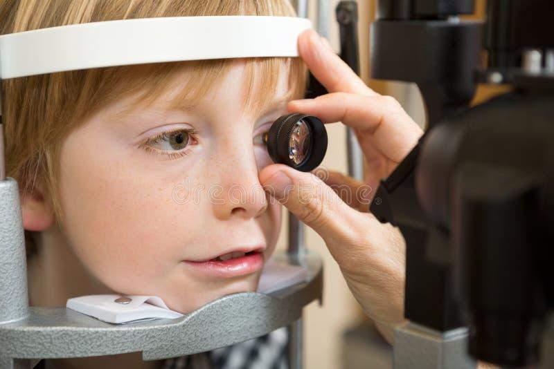 眼镜师的手审查的男孩的视网膜 免版税库存图片