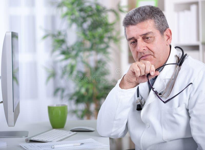戴眼镜的严肃的现代资深医生在办公室 免版税库存图片