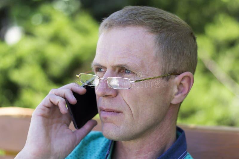 戴眼镜的人与电话 库存图片