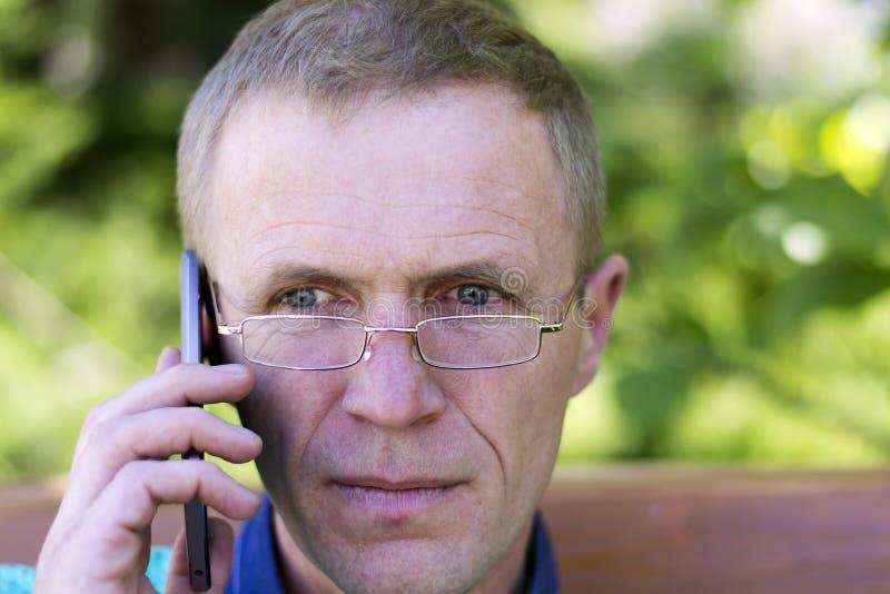 戴眼镜的人与电话 库存照片