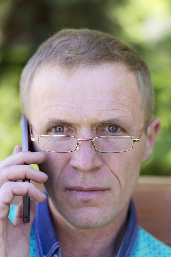 戴眼镜的人与电话 免版税库存照片