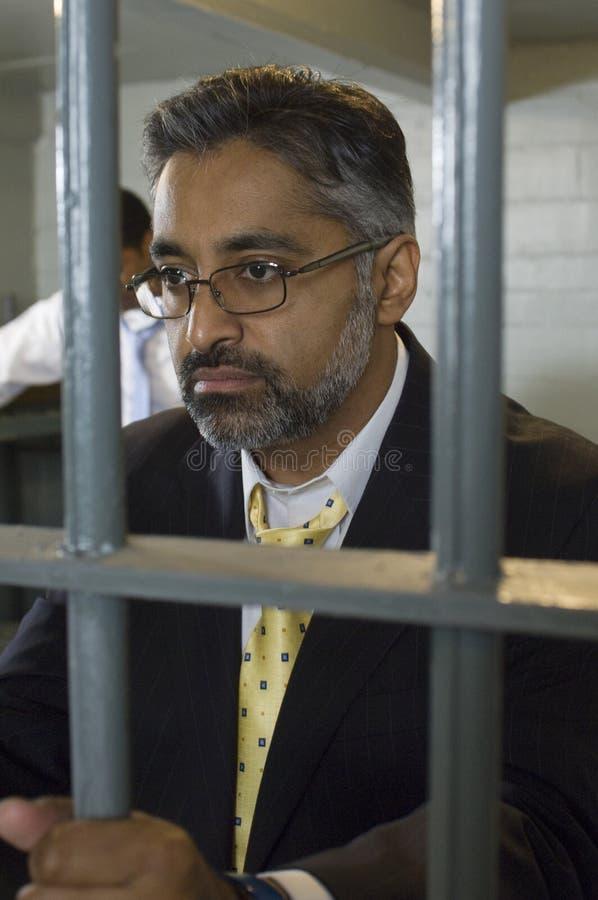 眼镜的人关在监牢里 免版税库存图片