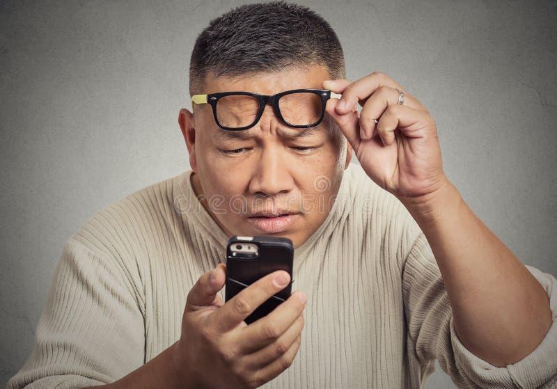 戴眼镜的人有麻烦看见电话的筛选视觉问题 库存图片