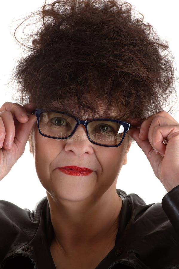 戴眼镜的卷曲成熟妇女 免版税图库摄影