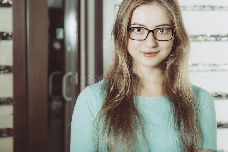 戴眼镜的妇女在光学沙龙 库存图片