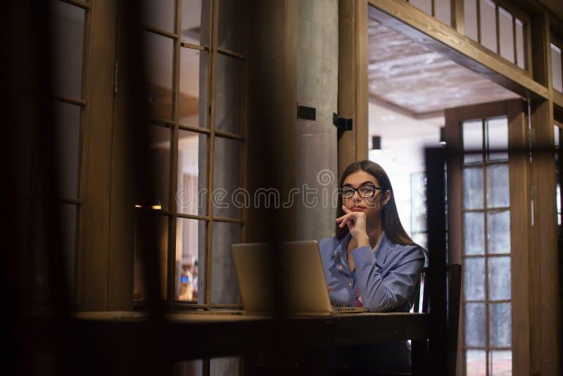 戴眼镜的妇女在屋子里 库存照片