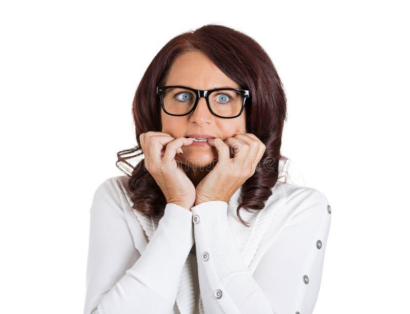 戴眼镜的害怕的急切妇女咬住指甲盖的 库存图片