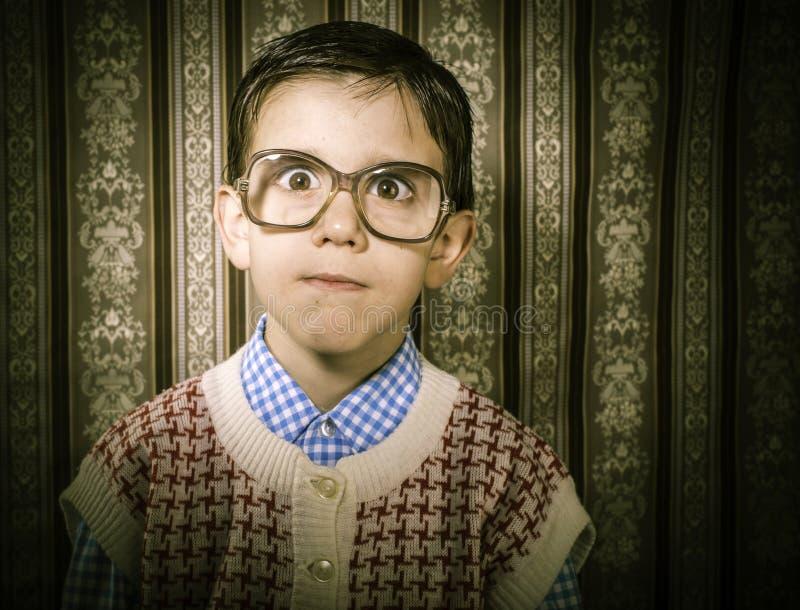 戴眼镜的微笑的孩子在葡萄酒衣裳 免版税库存图片