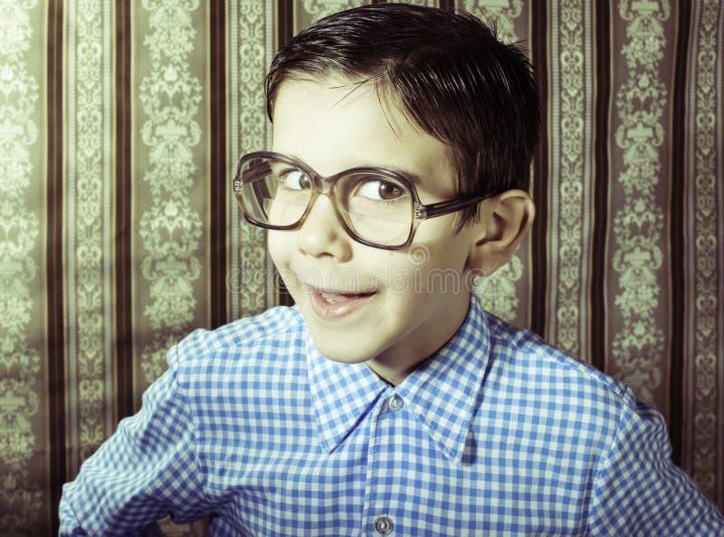 戴眼镜的微笑的孩子在葡萄酒衣裳 免版税库存照片