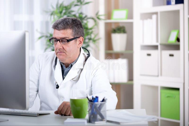 戴眼镜的微笑的现代资深医生在办公室 图库摄影