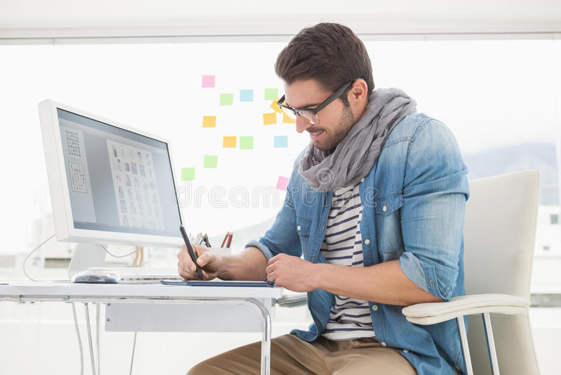 戴眼镜的微笑的设计师使用数字化器 免版税库存照片