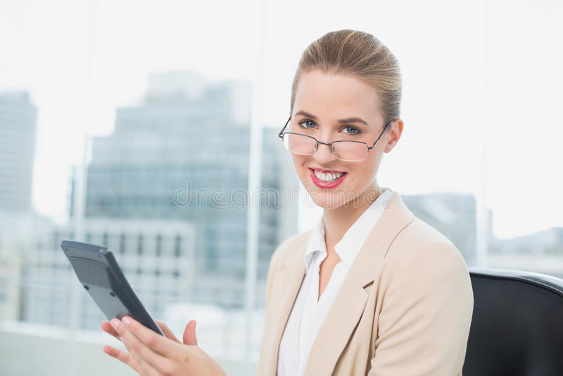 戴眼镜的快乐的女实业家使用计算器 库存照片