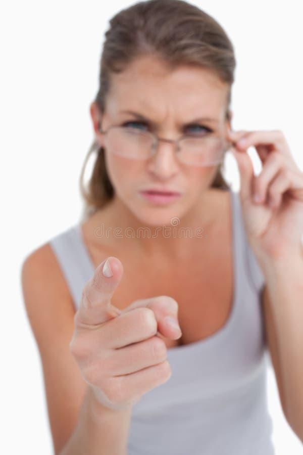戴眼镜的指向观察者的一名恼怒的妇女的画象 免版税库存图片