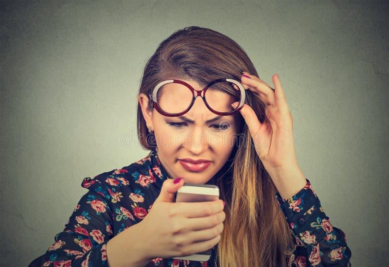 戴眼镜的特写妇女有麻烦看见手机的有视觉问题 库存照片
