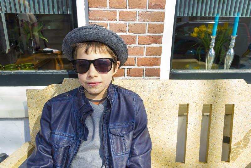 戴眼镜的男孩坐在房子前面的一条长凳 免版税库存照片