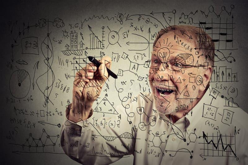 戴眼镜的老人科学家写与笔的秘诀 库存图片