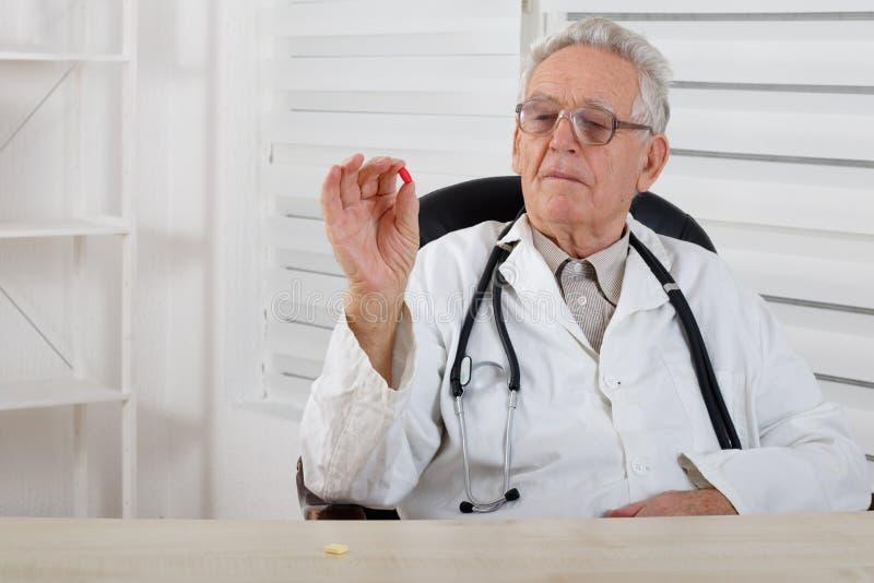 戴眼镜的老医生学习红色药片 免版税库存照片