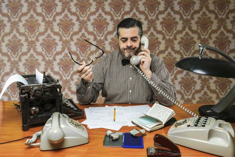 戴眼镜的雇员谈话在电话在办公室 库存照片