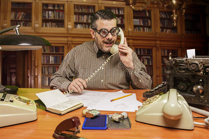 戴眼镜的雇员谈话在电话在办公室 库存图片