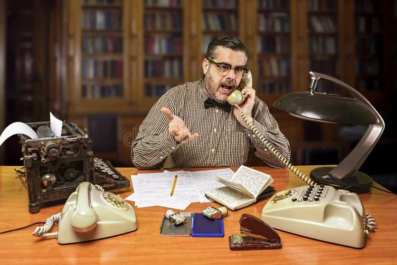 戴眼镜的雇员谈话在电话在办公室 免版税库存图片