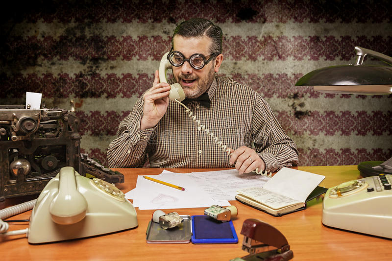 戴眼镜的雇员谈话在电话在的办公室 免版税库存图片